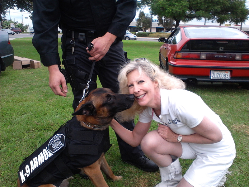 Fullerton PD K9 Mueller gives nose kisses of thanks to Suzanne Saunders, K-9 Armor Co-founder, photo by Tina Ortega North of Fullerton PD.